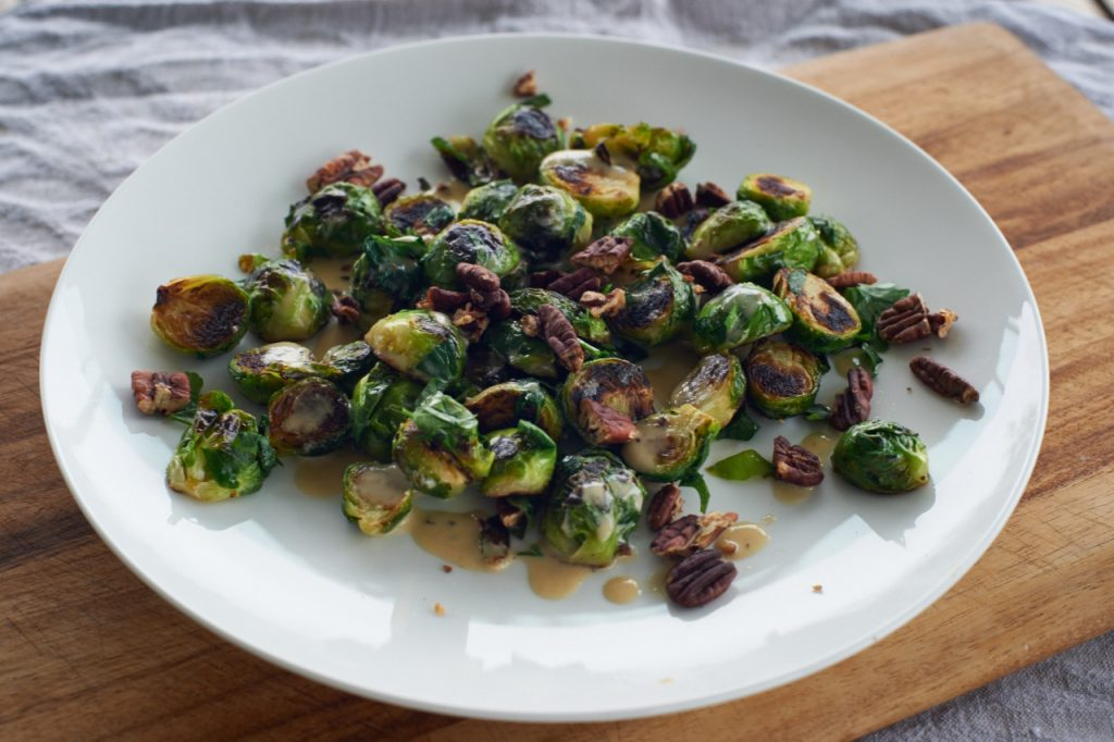 Fried sprouts with tahini dressing and pecans